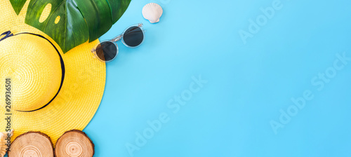 summer blue banner with yellow hat ,sunglasses,seashell and monstera leaf on blue background top view. - 269936501