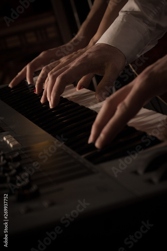 Fototapety, obrazy: Four hands on the keys of the synthesizer shot with a shallow depth of field