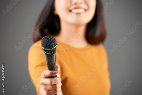 Woman giving young microphone