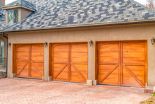 Luxurious Exterior Of A House With Stylish Brown Wooden Garage Doors