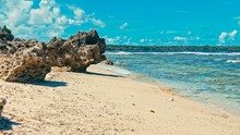 Sandy Sea Score Beach On A Small Tropical South Pacific Island With Large Rocks And Green Vegetation And Crystal Clear Water