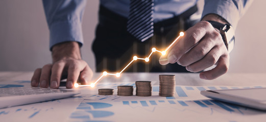 Man stacking coins with a graph of profit.