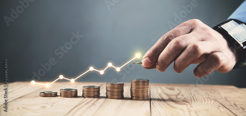Fototapeta  Man stacking coins with a graph of profit. obraz