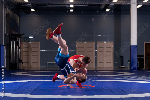 Fototapety, obrazy: Two strong wrestlers in blue and red wrestling tights are wrestlng and making a  making a hip throw  on a yellow wrestling carpet in the gym. Young man doing grapple.