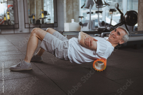 Cheerful senior man smiling to the camera, using foam roller on his back Fototapet