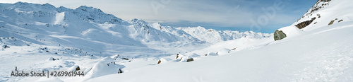 Leinwand Poster Panoramic view across snow covered alpine mountain range