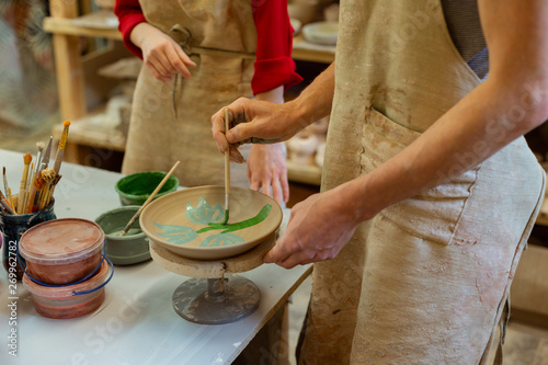 Focused interested pottery master finishing production of plate Fototapeta