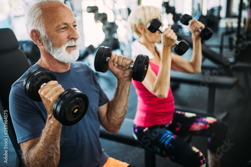 Fotografía  Mature fit couple exercising in gym to stay healthy