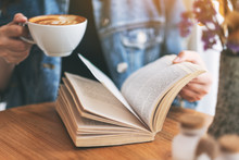 Closeup Image Of A Woman Holding And Reading A Vintage Novel Book While Drinking Coffee