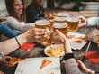 canvas print picture - Group of friends toasting with a glass of beer while eating pizza - Millennials have fun together - Day of happiness between young men and women