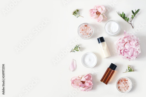 Styled beauty composition. Skin cream jar, tonicum bottle, roses, peony flower and Himalayan salt on white table background. Organic cosmetics, spa concept. Empty space, flat lay, top view.