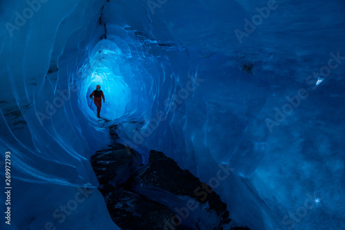 Photo Stands Night blue Guide inside an ice cave on a glacier in Alaska. Glacier caves are rare on teh Matanuska, but this one runs deep into the ice.
