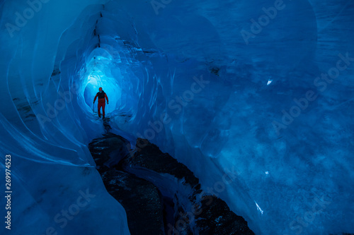 Poster Bleu nuit Man walking through a tunnel of an ice cave in Alaska. Glacier caves on the Matanuska Glacier in the Chugach Mountains.