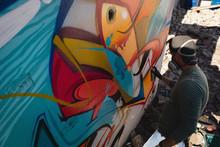 Graffiti Artist Spray Painting On Weathered Wall