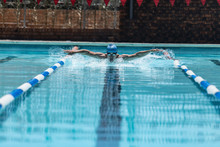 Young Caucasian Male Swimmer Swimming Butterfly Stroke In Swimming Pool