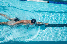 Young Caucasian Male Swimmer Swimming Freestyle In Swimming Pool