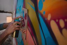 Graffiti Artist  Spray Painting On Card Board At Alley