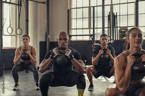 Poster Fitness Fitness people squatting with kettlebell