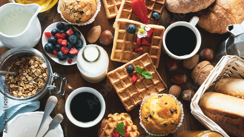 Health and colorful breakfast - cups of coffee with  granola, waffles, muffins,almond,hazelnuts,various fresh fruits, berries and milk on old wooden table. Health food concept .Top view. - 269981984