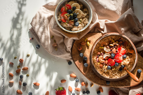 Oatmeal porridge in coconut bowl with wooden spoon on natural wooden tray. Porridge oats with strawberry, pistachios, blueberry, almond and banana. Shadow of sunrise morning. Top view or flat lay - 269986350