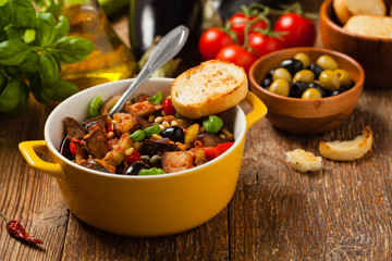 Traditional Italian caponata, served with croutons in a yellow, sunny pot. Decorated with basil and pine nuts.