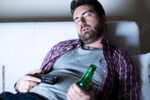 Obraz Lazy man watching television at night alone - fototapety do salonu