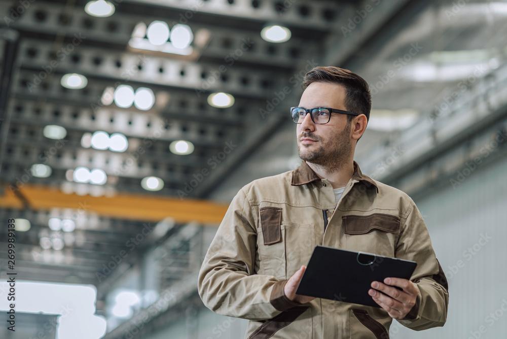 Leinwandbild Motiv - bnenin : Portrait of a factory supervisor at work, low angle view.