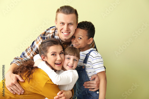 Photo Happy couple with little adopted children on color background