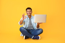 Handsome Man With Laptop Showing OK On Color Background