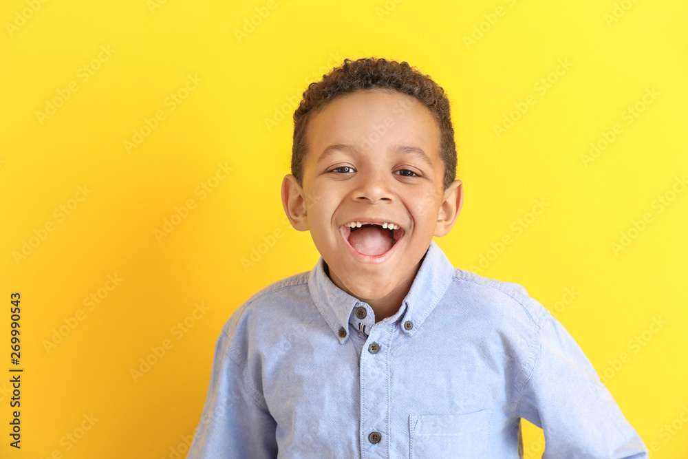 Fototapeta Laughing African-American boy on color background