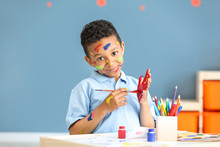 Cute African-American Boy With Hands And Face In Paint At Home