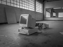 Italy - May 2019: Old Generation Computer Destroyed And Abandoned In An Old Dirty Warehouse With No People, Black And White.