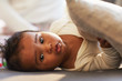 Portrait of adorable African baby boy with puffy lips lying on comfortable sofa in living room and holding pillow