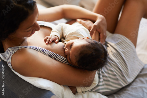 Fotografía Close-up of serene loving young black mother in nightgown sitting on bed and bre