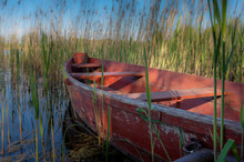 Wooden Red Rowboat Moored To A Rustic Jetty