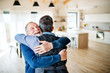 canvas print picture An adult hipster son and senior father indoors at home, hugging.