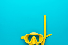 Flat Lay Shot Of Yellow Diving Mask With Snorkel Over Turquoise Blue Background. Minimalist Photo Concept Of Dive Mask And Snorkel With Copy Space