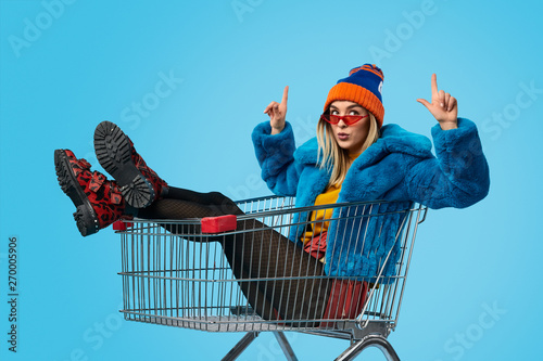 Foto Weird female in shopping cart pointing up