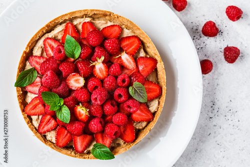 Tela Whole berry tart with raspberries, strawberries and cream on white dish, top view