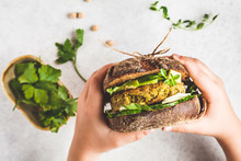 Vegan Sandwich With Chickpea Patty, Avocado, Cucumber And Greens In Rye Bread In Children's Hands.