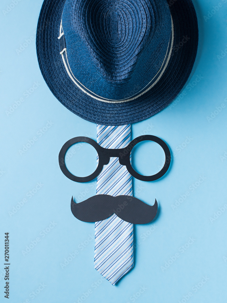 Fototapeta Fathers day concept with hat, glasses and tie on blue background - obraz na płótnie