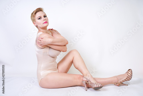 curvaceous caucasian young woman in beige tight shapewear on white background in Studio