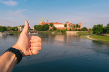 Closeup Of Male Hand Showing Thumbs Up Gesture At Wawel Castle In Cracow City, Poland, On Background.