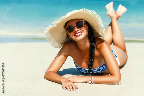 fototapeta na drzwi i meble Journey. Young beautiful lady in a straw hat, sunglasses is lying on the sand of the sea shore smiling, resting, traveling