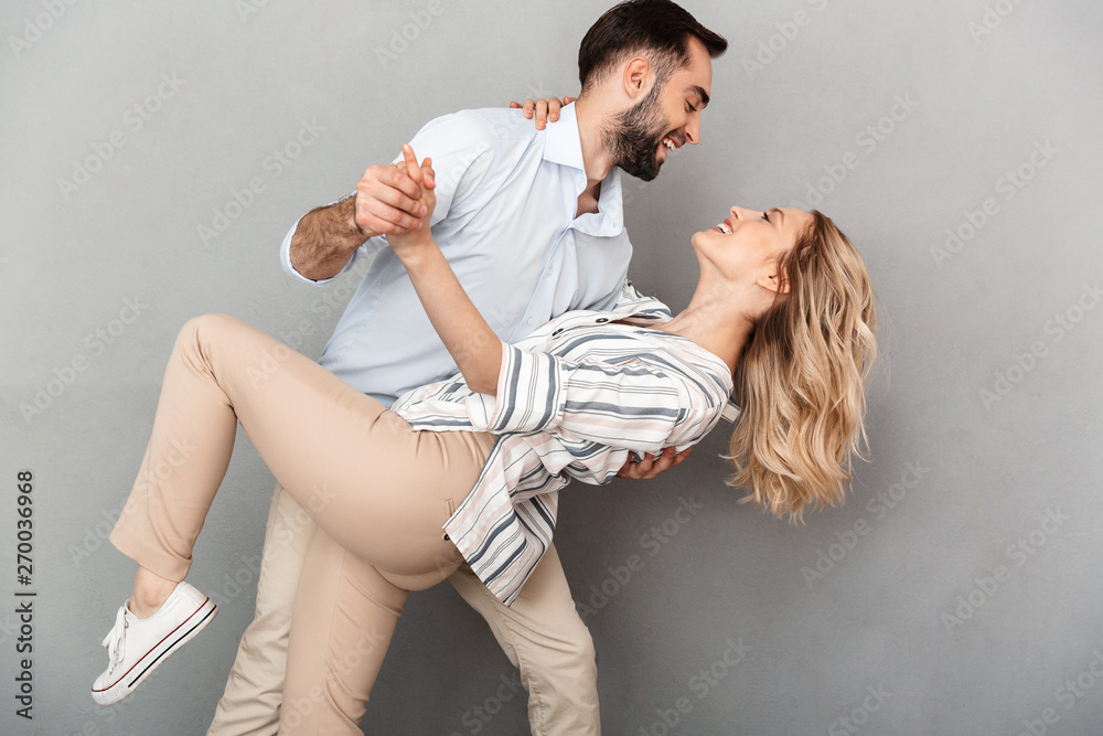 Fototapeta Photo closeup of romantic couple in casual clothing smiling and dancing
