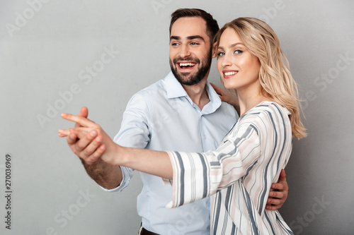 Photo closeup of smiling couple in casual clothing looking at camera and dancing - 270036969