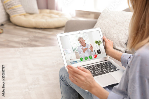 Fotografie, Obraz  Young woman using video chat on laptop in living room, closeup