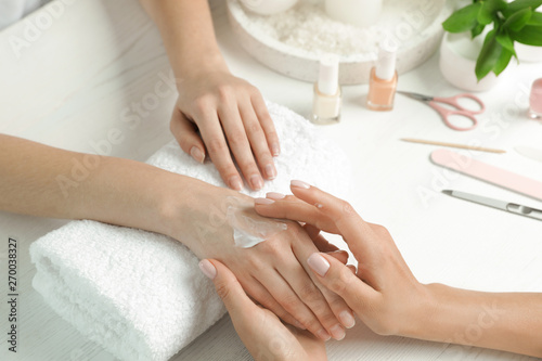 Poster Spa Cosmetologist applying cream on woman's hand at table in spa salon, closeup