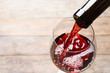 Pouring red wine from bottle into glass on blurred background, closeup. Space for text