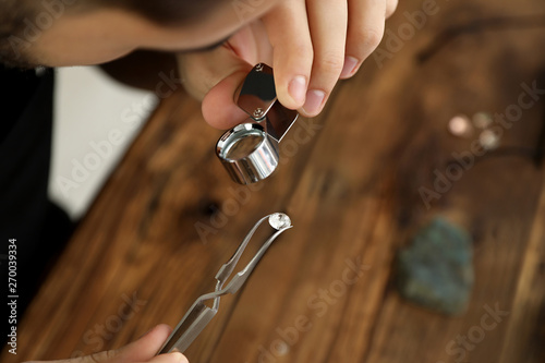 Male jeweler evaluating precious gemstone at table in workshop, closeup